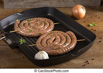 Raw sausages on a grilled pan