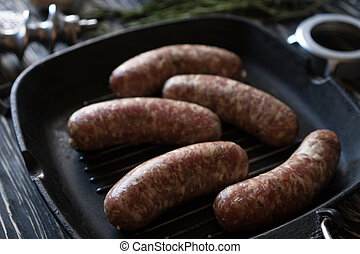 raw sausages on a pan