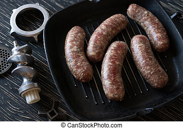 raw sausages on the pan and old meat grinder parts