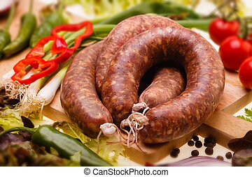 raw sausages, with vegetables on wooden board