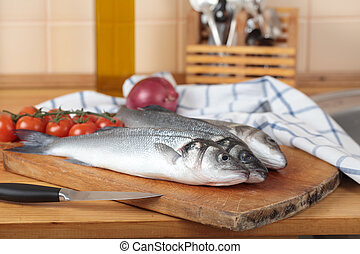 Raw sea bass on a wooden cutting board