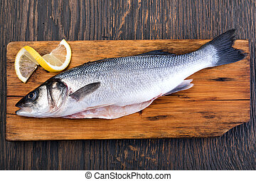Raw Seabass isolated on a wooden table