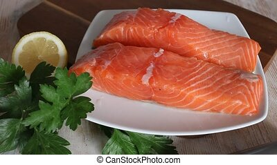 Uncooked fillet salmon fish with parsley and garlic on wooden table