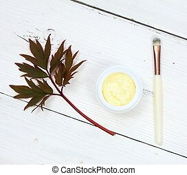 Good for smooth and healthy skin. White wooden table, cosmetic brush.