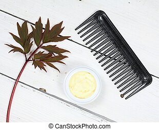 Good against dry and damaged hair. White wooden table, black comb.
