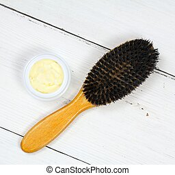 Good for dry and damaged hair. White wooden table, hairbrush.
