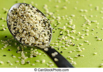 Close up of organic hemp seeds on silver spoon sitting on green background