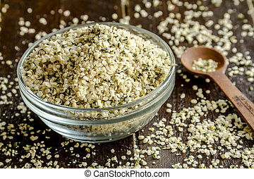 Organic hemp seeds in glass bowl on wooden table with measuring spoon