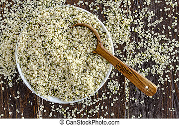 Organic hemp seeds in white bowl with measuring spoon on wooden table
