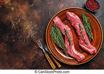 Raw skirt machete beef meat steak on a plate. Dark background. Top view. Copy space