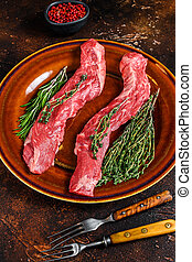 Raw skirt machete beef meat steak on a plate. Dark background. Top view