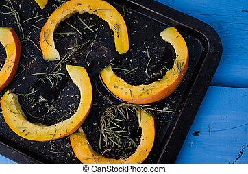 Raw sliced pumpkin on a baking tray