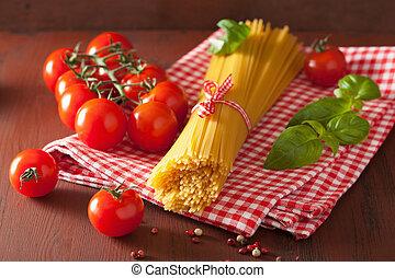 raw spaghetti pasta basill tomatoes. italian cuisine in ...