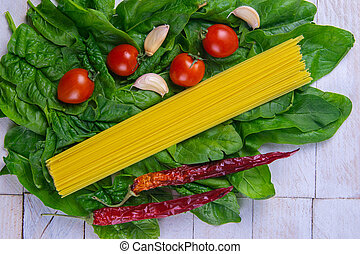 Raw spaghetti with tomatoes and spicy red pepper stand on spinach leaves on a white wooden table