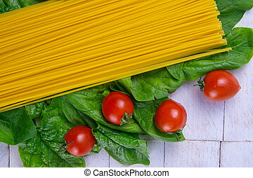 Raw spaghetti with tomatoes stand on spinach leaves on a white wooden table