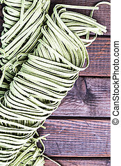 Raw spinach fettuccine pasta on wood tabel. Background