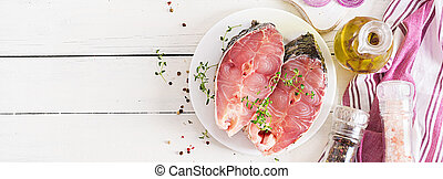 Raw steak of carp fish with lemon and thyme on white wooden background. Preparing fish for roasting in parchment paper. Diet menu. Top view. Banner. Flat lay