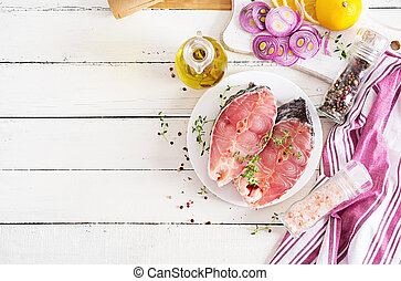 Raw steak of carp fish with lemon and thyme on white wooden background. Preparing fish for roasting in parchment paper. Diet menu. Top view. Flat lay