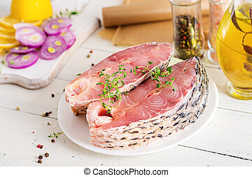 Raw steak of carp fish with lemon and thyme on white wooden background. Preparing fish for roasting in parchment paper. Diet menu.