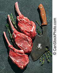 Raw steak with a meat cleaver on a dark stone background.