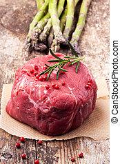 raw steak with asparagus on wood