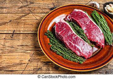 Raw strip loin beef meat steak on a plate with herbs. wooden background. Top view. Copy space