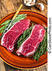 Raw strip loin beef meat steak on a plate with herbs. wooden background. Top view