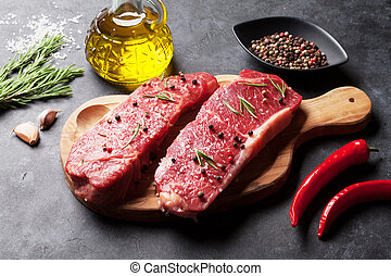 Raw striploin steak with rosemary, salt and pepper cooking ...