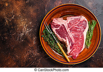 Raw T-bone beef meat Steak with herbs on a plate. Dark background. Top view. Copy space