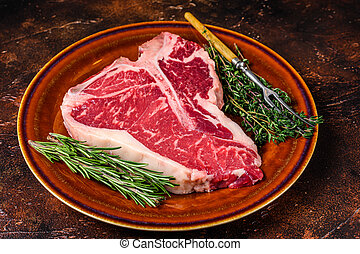 Raw T-bone beef meat Steak with herbs on a plate. Dark background. Top view