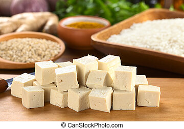 Raw tofu cut in dices on wooden board with rice and other...