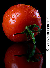 Raw tomato on black background - Fresh raw tomato with ...
