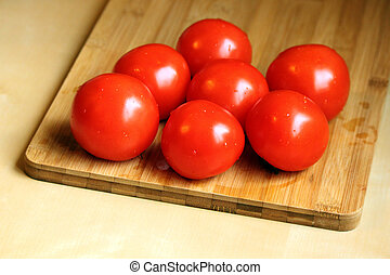 Raw tomatoes on the wooden chopping board