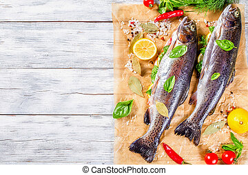 raw trout on a cutting board with lemon, top view