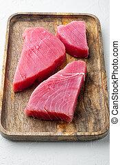 Raw tuna steak, on wooden tray, on white stone background