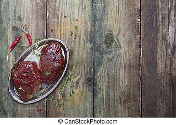 Raw uncooked beef steak meat with pepper spices on top view...