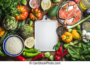 Raw uncooked salmon fish in small metal plate with vegetables, rice, herbs, spices, olive oil on rustic wooden background, white ceramic board in center, copy space, top view