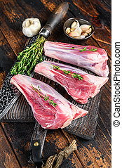 Raw veal shanks meat on a cutting board with herbs. Dark wooden background. Top view