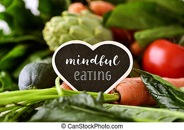 raw vegetables and text mindful eating - closeup of a heart-...