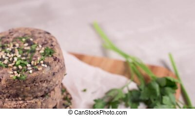 Raw veggie burger with black beans with parsley leaves on...