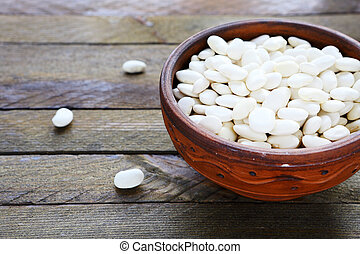 raw white beans in a ceramic bowl