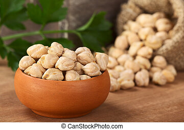 Raw white dried chickpeas (lat. Cicer arietinum) in small...