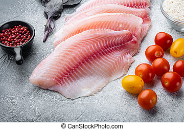 Raw white fish tilapia with basmati rice and cherry tomatoes ingredients, on gray background