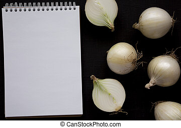 Raw white onions, blank notepad on a black background, top view. Flat lay, overhead, from above. Copy space.