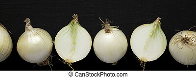 Raw white onions on a black background, top view. Flat lay, overhead, from above.