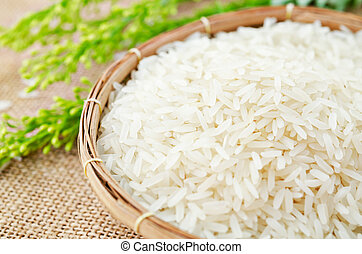 Raw white rice and wooden spoon in weave basket.