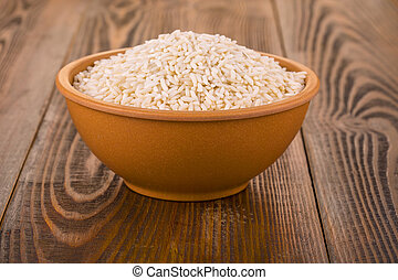 raw white rice in a Cup on a wooden table.