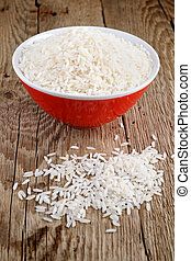 Raw white rice in bowl on wooden table