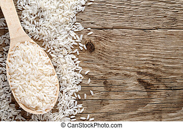 Raw white rice in spoon on wooden background