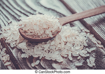 white rice in spoon on wooden background